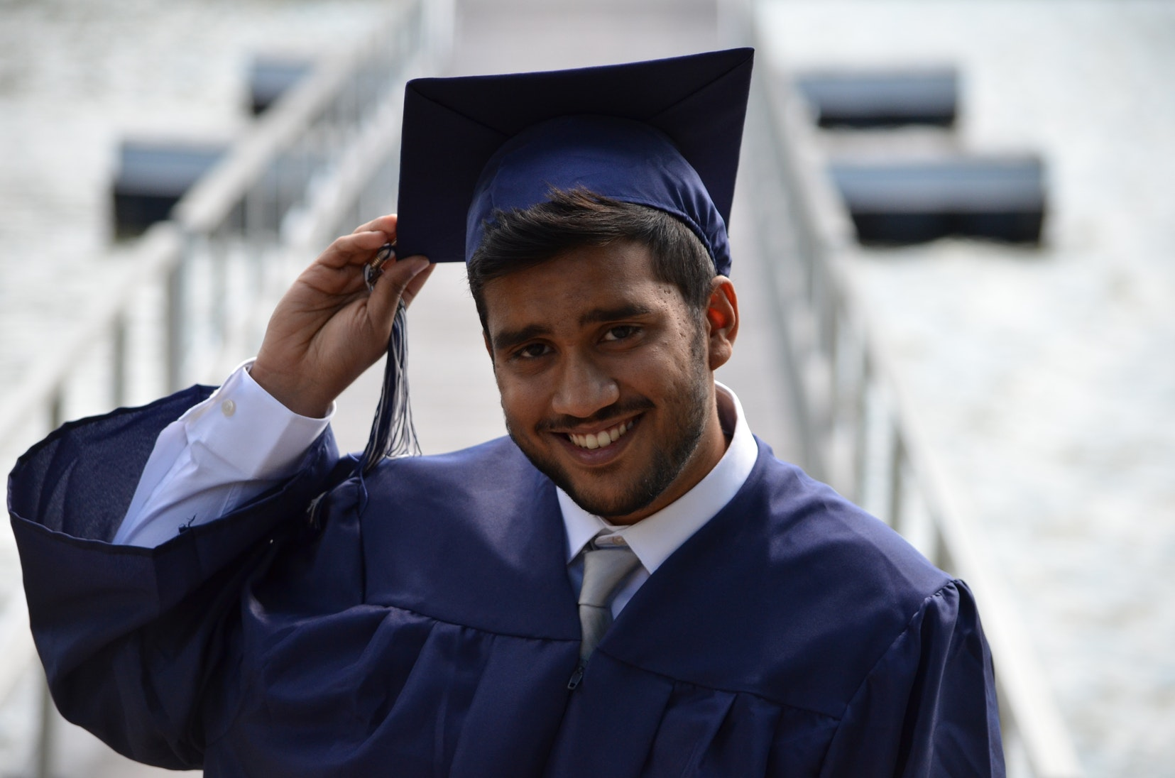 A picture of a graduate holding their hat and smiling.