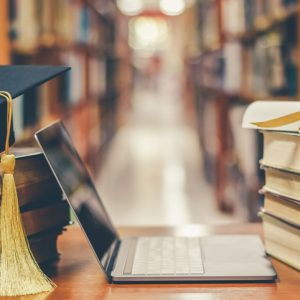 E-learning class and internet online education success with IT computer laptop, graduation hat, academic cap, mortarboard and degree certificate on books in class or library study room