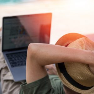 Easy relax business man lifestyle with computer in hotel resort sitting hands behind head for happy businessman people with work life balance. Simplify Your Life Week. International happiness day.