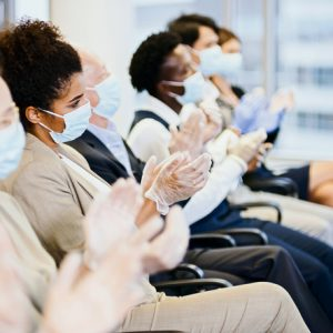 Applause after seminar. People wearing masks during pandemic