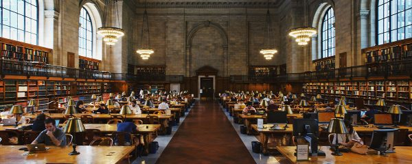 A panoramic shot inside an old library showing people reading and studying at desks.
