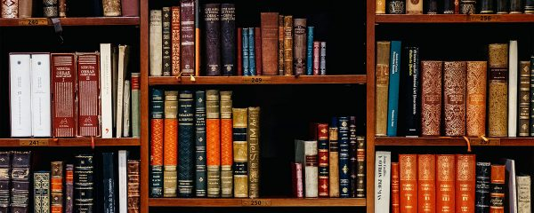 A book case with many different books in it.
