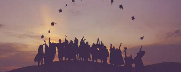 A picture of a group of graduates throwing their hats so they make a semi-circle in the air.