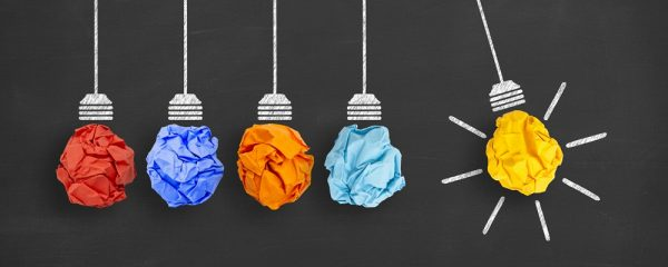 A artistic creation of five light bulbs made from crumpled up pieces of paper with different colours. The last light bulb on the right is yellow and is swinging out and signally it is on to symbolise an idea.